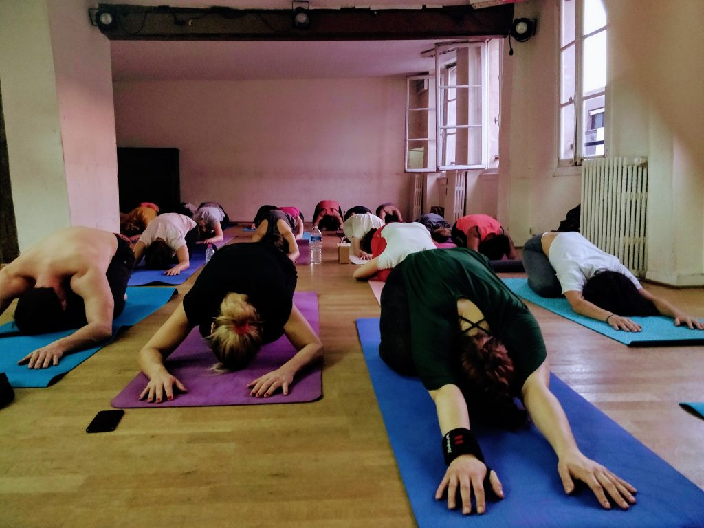 Yogis in child's pose at Salles Saint Roch, a popular spot for diverse and affordable yoga in Paris